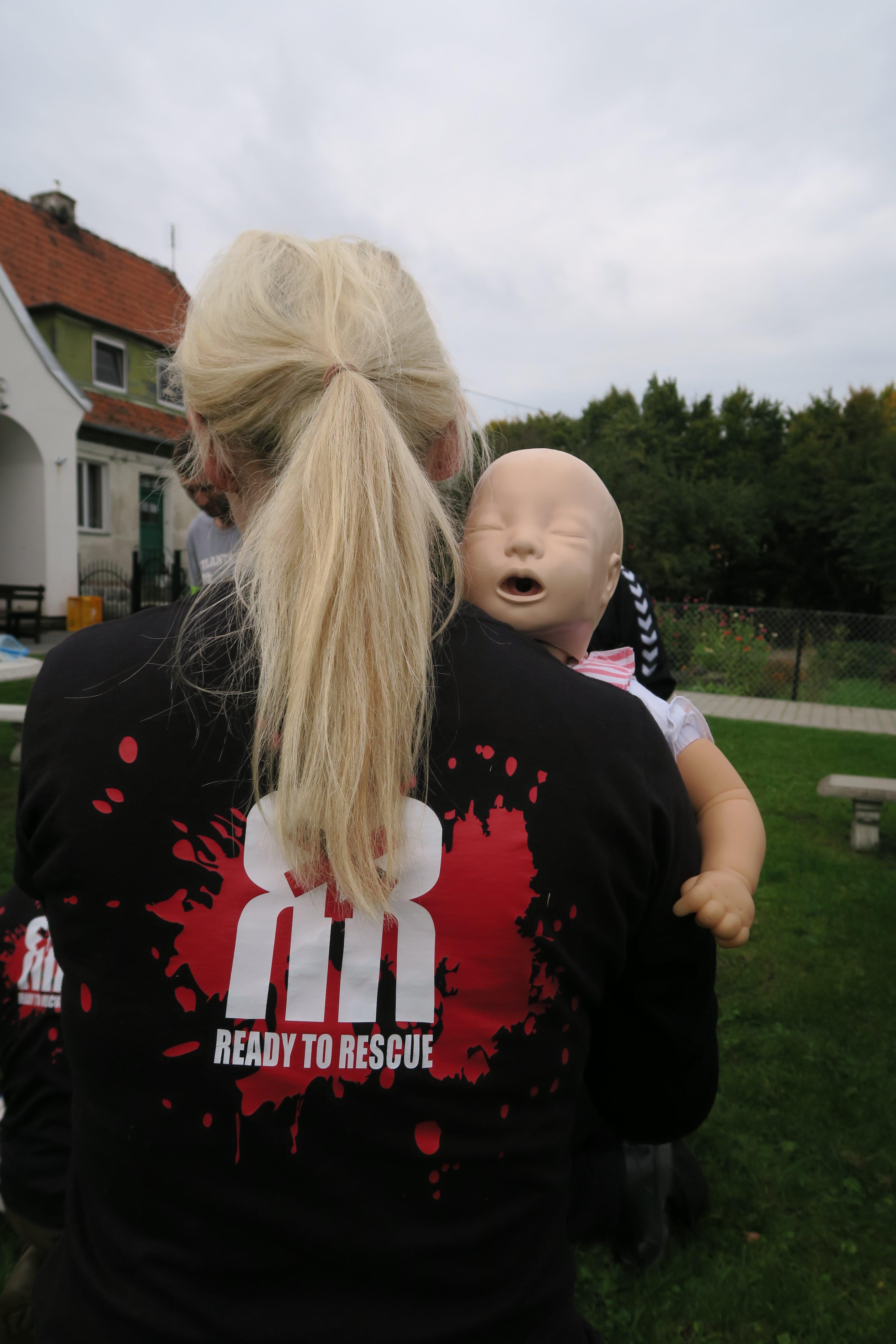 25.pierwsza pomoc małe dziecko, BLS dziecka, matka pomaga dziecku class=